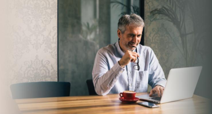Homme d'âge mûr en train de lire une publication financière sur son ordinateur portable