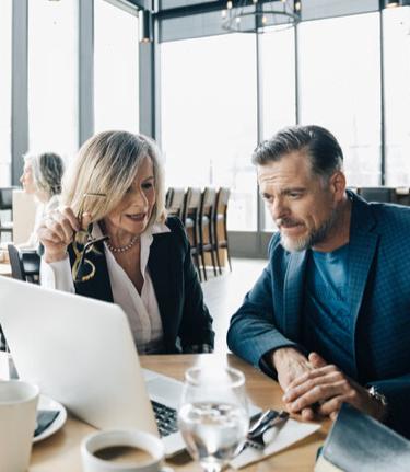 Conseillère en placement, l'air serein, qui lit avec son client des informations financières sur un ordinateur portable.