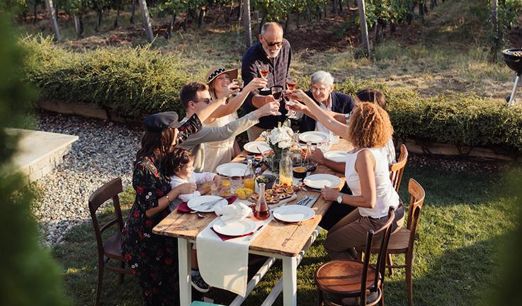 Une famille qui trinquent autour d'une table dans une cour.