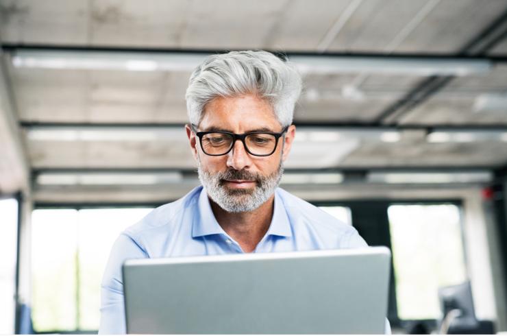 Un homme, cheveux grisonnants et lunettes, face à son ordinateur portable