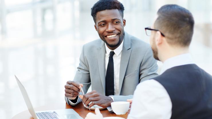Jeune conseiller avec son client en pleine discussion, assis dans un café